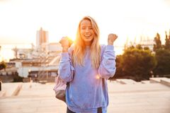 Portrait of a happy young girl with backpack. Standing outdoors during sunset, holding mobile phone, celebrating Stock Photo