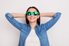 Portrait of happy young girl in bright sunglasses with hands behind the head on white background royalty free stock photos