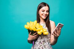 Portrait of a happy young girl in dress use mobile phone while holding big bouquet of yellow tulips isolated over color background stock image