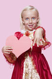 Portrait of a happy young girl dressed in princess costume holding paper heart as she displays ring over pink background Stock Photography