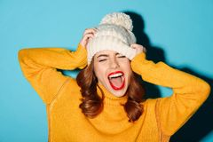 Portrait of a happy young girl dressed in winter hat. Laughing  over blue background Stock Photos