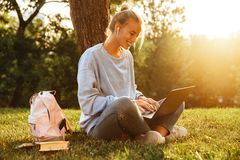 Portrait of a happy young girl in earphones with backpack. Sitting with legs crossed on a grass at the park, using laptop computer Stock Photography