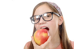 Portrait of happy young girl eating an apple over white backgro Stock Photography