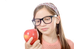 Portrait of happy young girl eating an apple over white backgrou Stock Photo