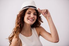 Girl in the studio. Portrait of a happy young girl with a hat on a white background smiling at the camera stock photography