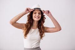 Girl in the studio. Portrait of a happy young girl with a hat on a white background smiling at the camera royalty free stock images