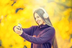 Portrait of happy young girl with headphones and smartphone in autumn park listening music or makes selfie.  Royalty Free Stock Images
