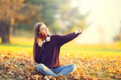 Portrait of happy young girl with headphones and smartphone in a. Utumn park listening music or makes selfie Stock Photos