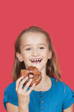 Portrait of happy young girl holding donut against red background Royalty Free Stock Photography