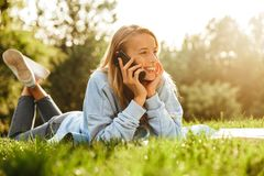 Portrait of a happy young girl laying on a grass. At the park, talking on mobile phone Stock Photos