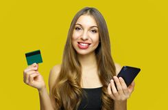 Portrait of a happy young girl showing plastic credit card while holding mobile phone isolated over yellow background stock photos
