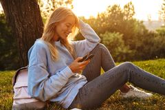 Portrait of a happy young girl sitting on a grass at the park. Using mobile phone Stock Image