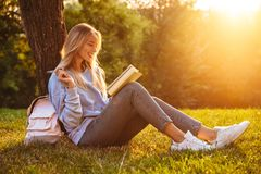 Portrait of a happy young girl sitting on a grass. At the park, reading a book, taking notes Royalty Free Stock Image