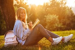 Portrait of a happy young girl sitting on a grass. At the park, reading a book, taking notes Stock Photos