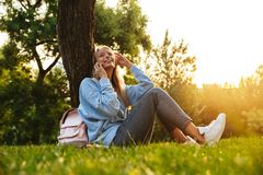 Portrait of a happy young girl sitting on a grass. At the park, talking on mobile phone Royalty Free Stock Photography