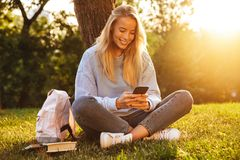 Portrait of a happy young girl sitting. On a grass at the park, using mobile phone Royalty Free Stock Photography