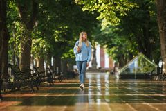 Portrait of a happy young girl student with backpack. And textbook walking at the park Stock Images