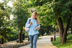 Portrait of a happy young girl student. With backpack and textbook walking at the park, holding mobile phone Royalty Free Stock Photography