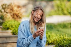 Portrait of a happy young girl student sitting on steps. Outdoors, looking at mobile phone Royalty Free Stock Photo