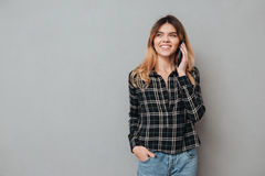 Portrait of a happy young girl talking on mobile phone. And looking away isolated over grey background Stock Photos