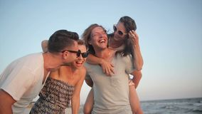 Portrait of happy young group of people enjoying beach holiday. Four friends are laughing near the sea during summer