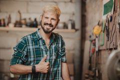 Portrait of happy young hipster bearded man by profession carpenter in the workshop. Portrait of happy young hipster bearded man by profession carpenter in the Stock Image