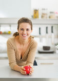 Portrait of happy young housewife with apple in modern kitchen Royalty Free Stock Images