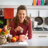 Portrait of happy young housewife putting money into piggy bank. After shopping on local market Royalty Free Stock Image