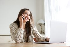 Happy young with laptop woman talking on cell phone. Portrait of happy young with laptop woman talking on cell phone Royalty Free Stock Photo