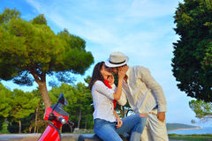 Portrait of happy young love couple on scooter enjoying themselves Stock Images