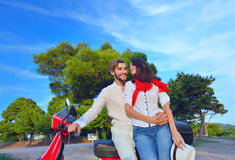 Portrait of happy young love couple on scooter enjoying themselves Stock Photos