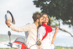 Portrait of happy young love couple on scooter enjoying themselves in a park at summer time.  Royalty Free Stock Photography