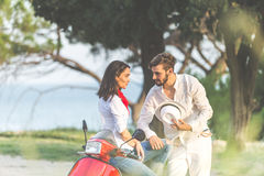 Portrait of happy young love couple on scooter enjoying themselves in a park at summer time.  Royalty Free Stock Photo