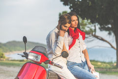 Portrait of happy young love couple on scooter enjoying themselves in a park at summer time.  Stock Photos