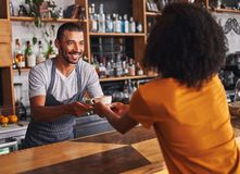 Male barista serves coffee cup to female customer in cafe stock images