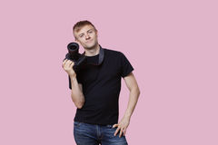 Portrait of a happy young male photographer holding camera over pink background Stock Images