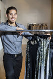 Portrait of a happy young male standing by clothes rack in fashion store Stock Photo