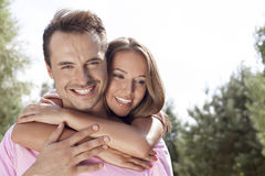 Portrait of happy young man being embrace by woman from behind in park Royalty Free Stock Image