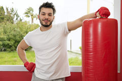 Portrait of happy young man doing physical exercise in gym Stock Photo