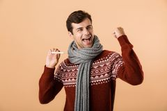 Portrait of a happy young man dressed in sweater. And scarf isolated over beige background, showing thermometer, celebrating stock image