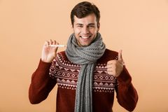 Portrait of a happy young man dressed in sweater. And scarf isolated over beige background, showing thermometer, showing thumbs up stock photos