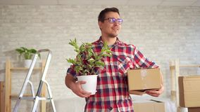 Portrait of a happy young man with a flower and a box in his hand, concept of moving. In modern apartment stock video footage