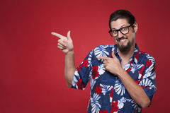 Portrait of a happy young man in Hawaiian shirt pointing sideway Stock Photography