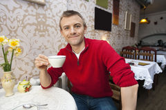 Portrait of happy young man holding coffee cup at cafe Royalty Free Stock Photography