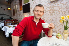 Portrait of happy young man holding coffee cup at cafe. Portrait of happy young men holding coffee cup at cafe Royalty Free Stock Photo