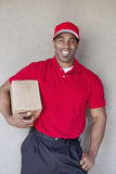 Portrait of a happy young man holding delivery box against wall Stock Images