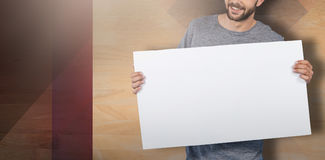 Composite image of portrait of happy young man holding placard Stock Photography