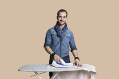 Portrait of a happy young man ironing shirt over colored background Stock Images