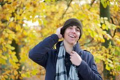 Portrait of a happy young man laughing outdoors with hat Stock Photo