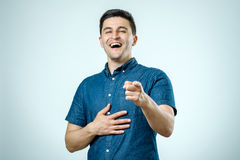 Portrait happy young man, laughing, pointing with finger at some Royalty Free Stock Photos